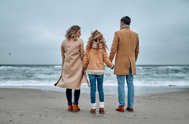 Jeune belle famille regarde la mer main dans la main, vêtue de foulards et de manteaux en hiver.