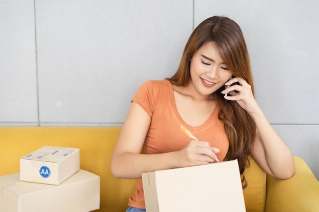 Jeune belle femme d'affaires asiatique heureuse en vêtements décontractés avec visage souriant utilise un smartphone et écrit le nom et l'adresse du client sur la boîte de colis à son bureau à domicile de démarrage, concept pme