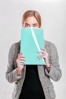 Jeune belle femme d'affaires blonde en robe noire, veste couvre son visage avec un dossier de papiers et de merveilles sur fond gris