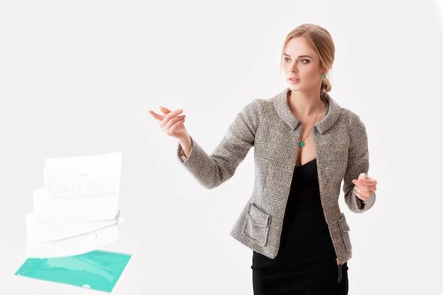 Jeune belle femme d'affaires blonde en robe noire, veste a laissé tomber un dossier de papiers sur fond gris