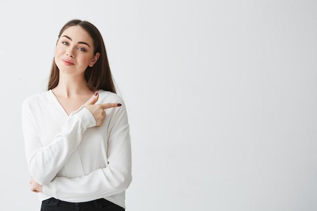 Jeune belle femme d'affaires brune souriant doigt pointé sur le côté.