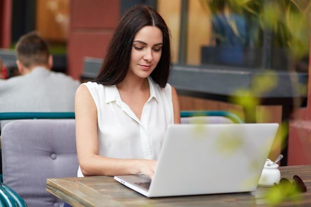 Jeune belle femme d'affaires brune vêtue de chemisier élégant blanc, est assis sur une cafétéria confortable en plein air, se trouve en face de l'ordinateur portable moderne ouvert, travaille au projet d'entreprise avant de se réunir