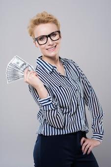 Jeune belle femme d'affaires détenant de l'argent isolé