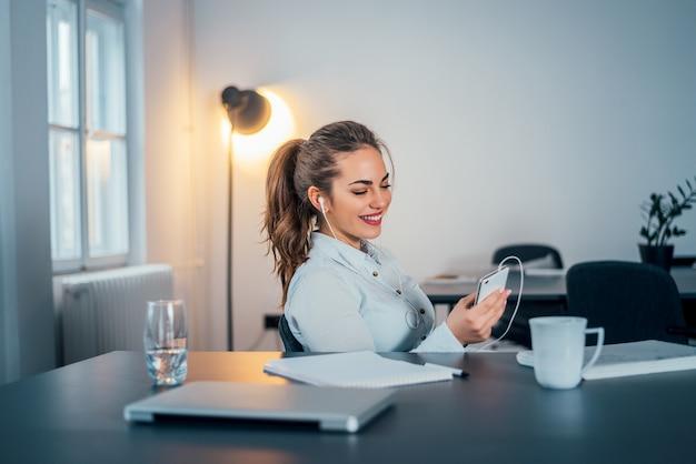 Jeune belle femme d'affaires écoutant de la musique dans son bureau.