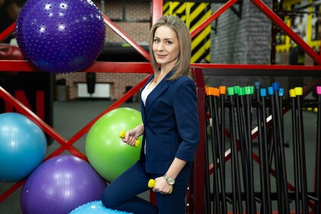 Jeune belle femme d'affaires avec des haltères dans la salle de gym.