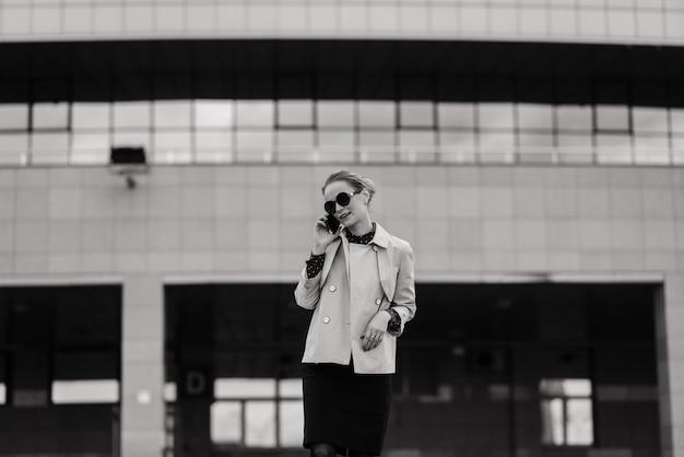 Jeune belle femme d'affaires avec des lunettes de soleil, téléphone dans les rues de la ville.