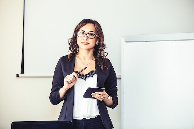 Jeune belle femme d'affaires réussie sur un écran blanc derrière le podium dans la salle de conférence.