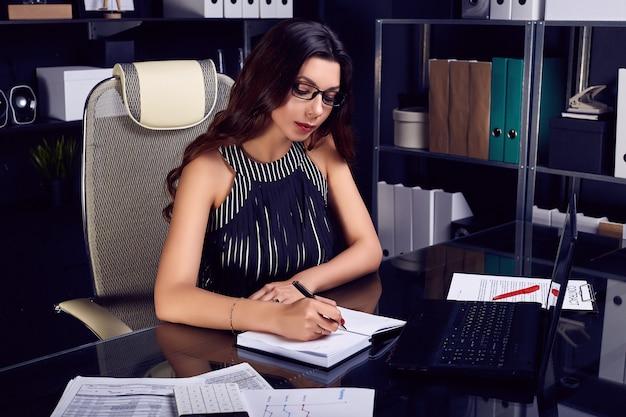 Jeune belle femme d'affaires travaillant au bureau noir élégant