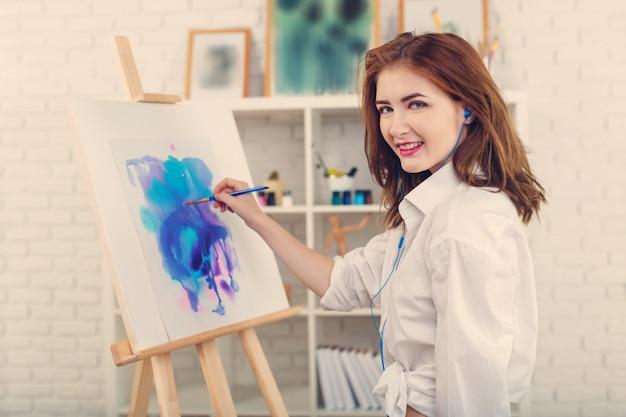 Jeune belle femme artiste dessinant une peinture abstraite sur un chevalet