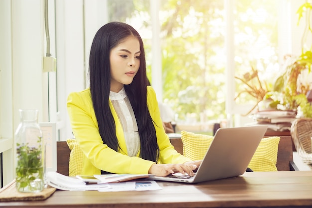 Jeune belle femme asiatique assise à table dans un café travaillant avec un ordinateur portable