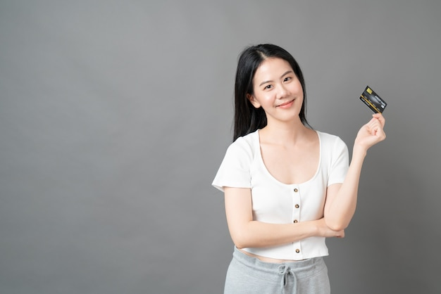 Jeune belle femme asiatique au visage heureux et présentant une carte de crédit en main montrant la confiance et la confiance nécessaires pour effectuer le paiement