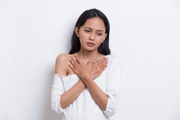 Jeune belle femme asiatique ayant une crise cardiaque isolée sur fond blanc