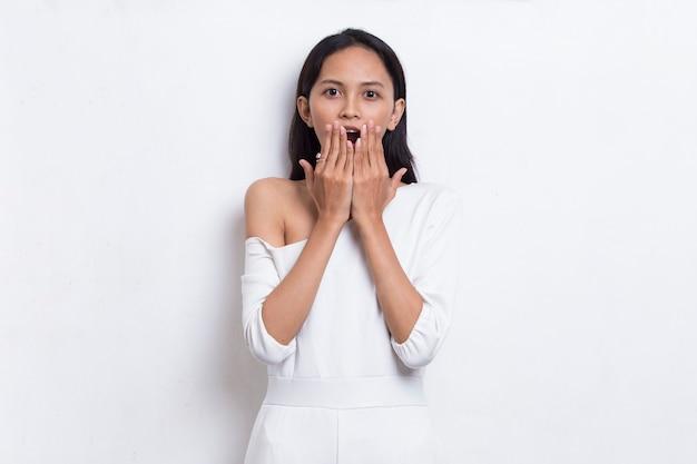Jeune belle femme asiatique choquée couvrant la bouche avec les mains pour erreur concept secret