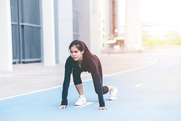 Jeune belle femme asiatique costume noir se prépare à commencer sur la piste de course.