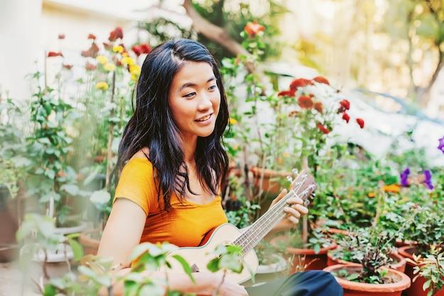 Jeune belle femme asiatique jouant du ukulélé sur son balcon