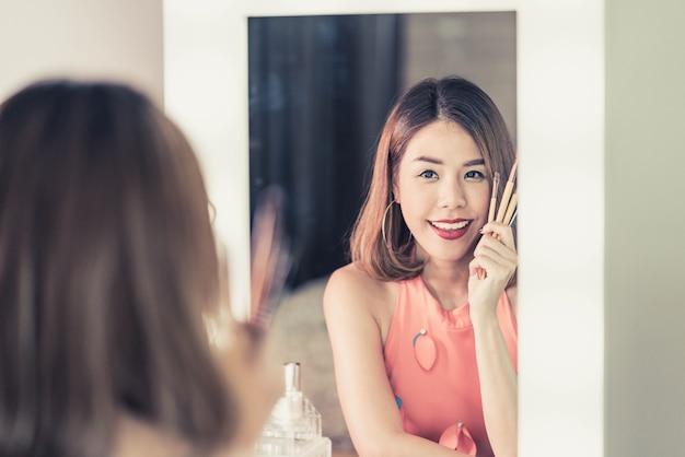 Jeune belle femme asiatique maquillant près d'un miroir