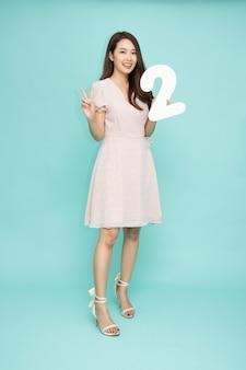 Jeune belle femme asiatique montrant le numéro 2 et pointant vers le haut avec le doigt numéro deux isolé sur fond vert, composition de personnes pleine longueur