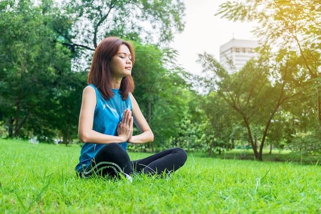 Jeune et belle femme asiatique pratiquant le yoga en plein air dans le parc avec une nature verdoyante backgro