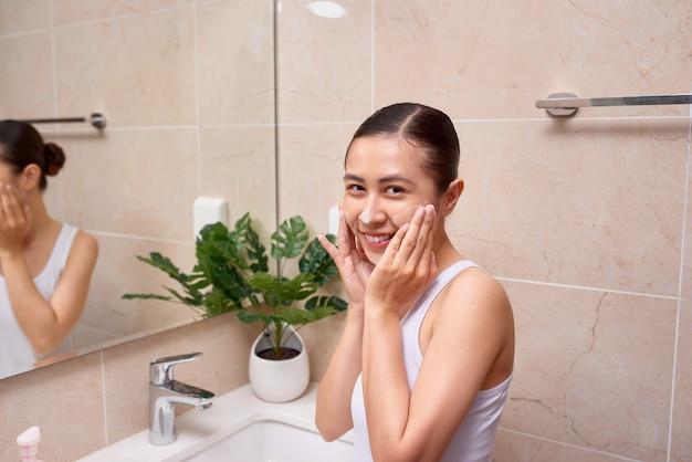 Jeune belle femme asiatique se lavant le visage avec les mains au savon
