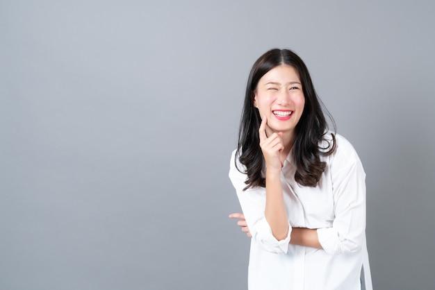 Jeune et belle femme asiatique avec un visage heureux et pensant en chemise blanche sur fond gris