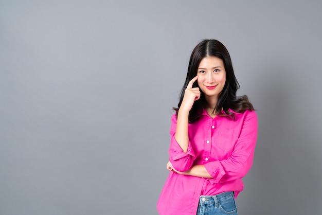 Jeune et belle femme asiatique avec un visage heureux et pensant en chemise rose sur fond gris