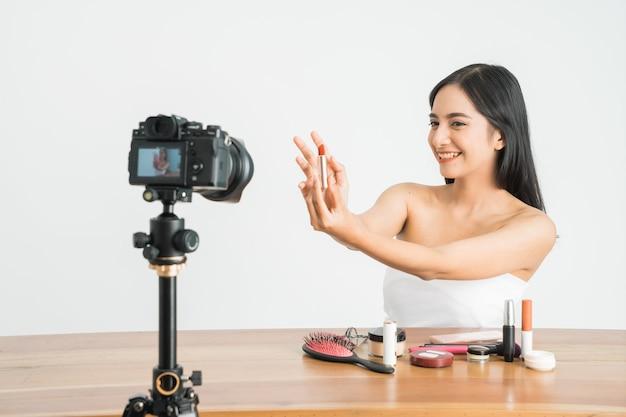 Jeune belle femme asiatique vlogger professionnel de beauté ou enregistrement de blogueur maquillage tutoriel à partager sur les médias sociaux sur un mur blanc