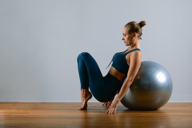 Jeune, belle femme athlétique, faire des exercices sur fitball dans la salle de gym. sportive femme slave dans un costume bleu et vert.