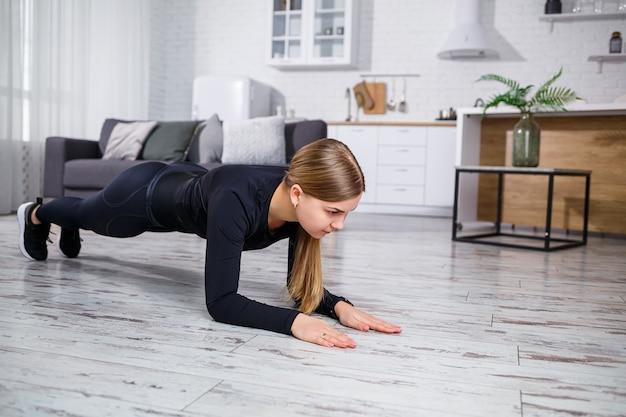 Jeune belle femme athlétique en leggings et haut faisant les exercices de planche. mode de vie sain. la femme fait du sport à la maison.