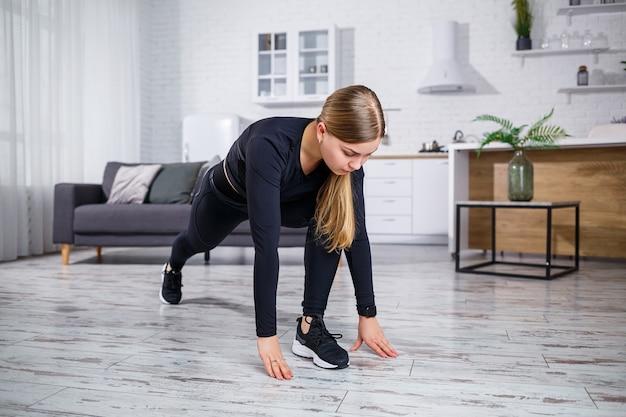 Jeune belle femme athlétique en leggings noirs et haut faisant des exercices d'échauffement à la maison. mode de vie sain. fille en vêtements de fitness. la femme fait du sport à la maison.