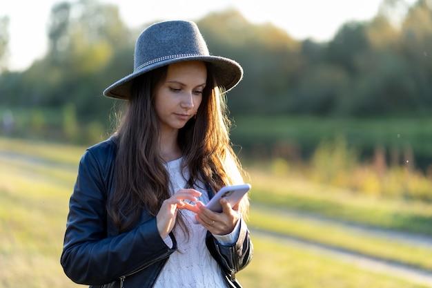 Une jeune et belle femme au chapeau sourit, regarde son smartphone et tape une réponse à un message dans le parc à la lueur brillante des rayons du coucher du soleil