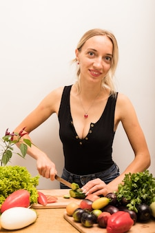 La jeune belle femme au foyer est occupée à préparer des aliments sains à la maison dans la cuisine