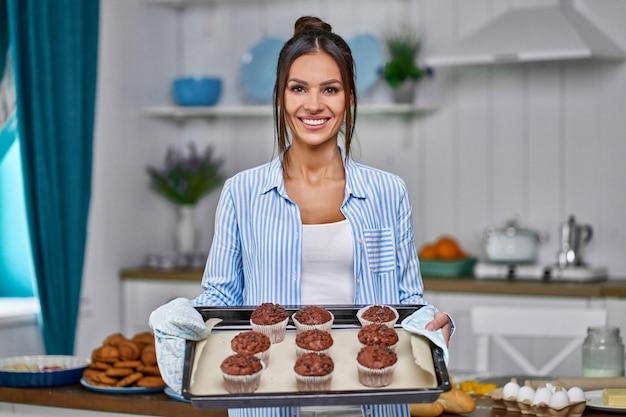 Jeune belle femme au foyer tenant des biscuits fraîchement cuits sur un plateau dans la cuisine