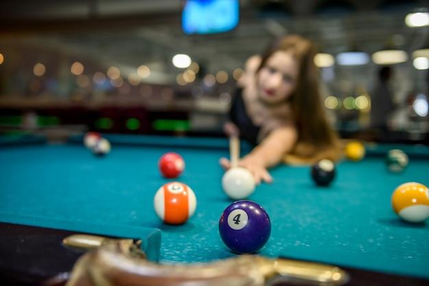 Jeune et belle femme au pub jouant au billard