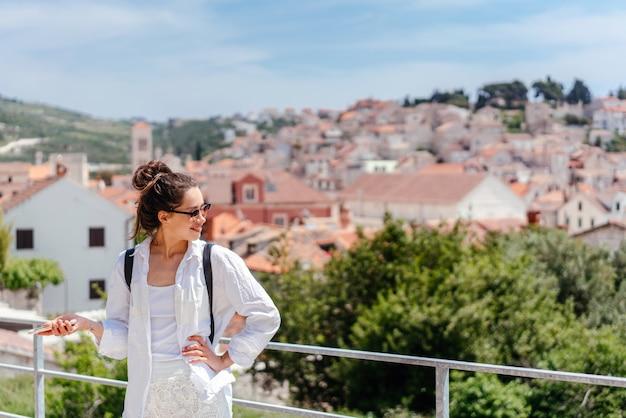 Jeune belle femme sur un balcon surplombant une petite ville de croatie