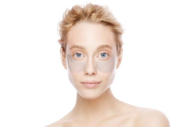 Jeune belle femme blonde aux yeux bleus avec des cache-œil pour éliminer les poches des yeux