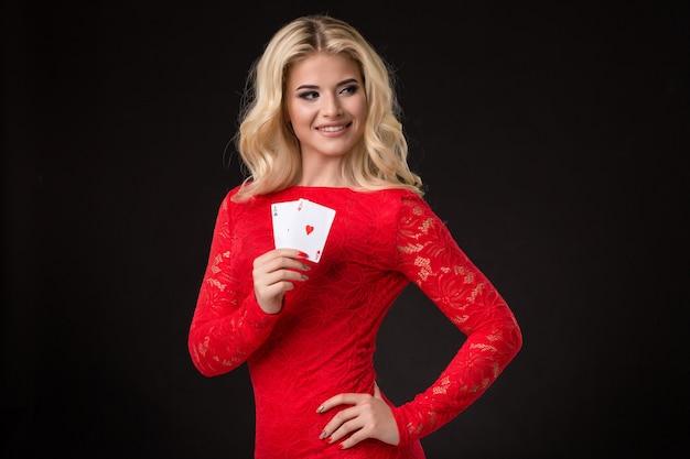 Jeune belle femme blonde avec des cartes à jouer au poker noir