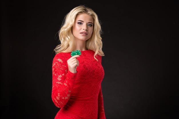 Jeune belle femme blonde avec des jetons de poker sur poker noir