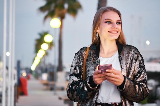 Jeune belle femme blonde marchant et écrivant des messages sms
