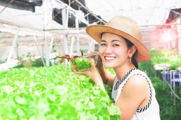 Jeune belle femme en bonne santé, tenant un bol de salade dans la ferme de légumes biologiques