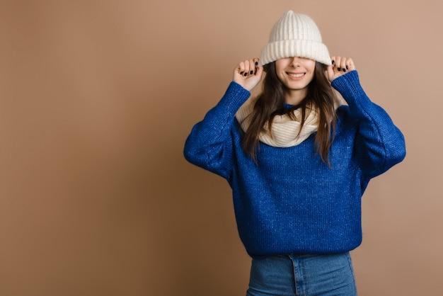 Jeune et belle femme avec un bonnet d'hiver tricoté sur ses yeux