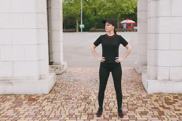 Jeune belle femme brune athlétique concentrée en uniforme noir et casquette faisant des exercices de sport, échauffement avant de courir, debout dans le parc de la ville à l'extérieur
