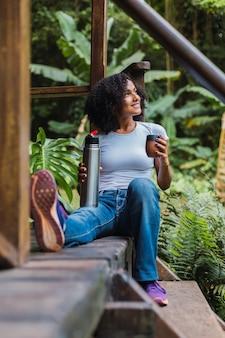 Jeune belle femme brune buvant l'infusion de compagnon dans une maison de campagne.