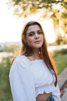 Jeune belle femme brune avec coucher de soleil en arrière-plan en regardant la caméra