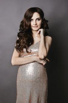 Jeune et belle femme brune enceinte avec un maquillage doux, dans la robe or brillant, souriant et posant sur le fond gris