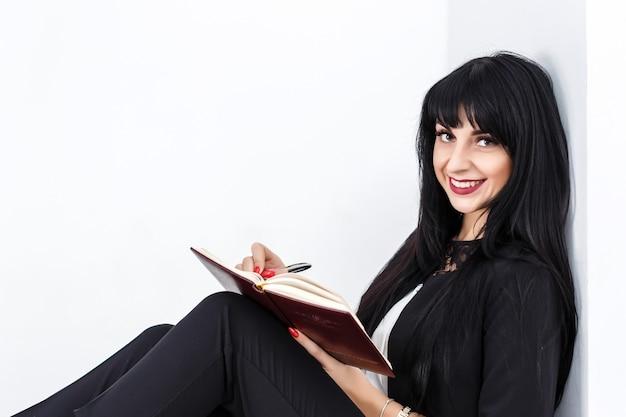 Jeune belle femme brune heureuse tenant un cahier vêtu d'un costume noir assis sur un sol au bureau, souriant, regardant la caméra.