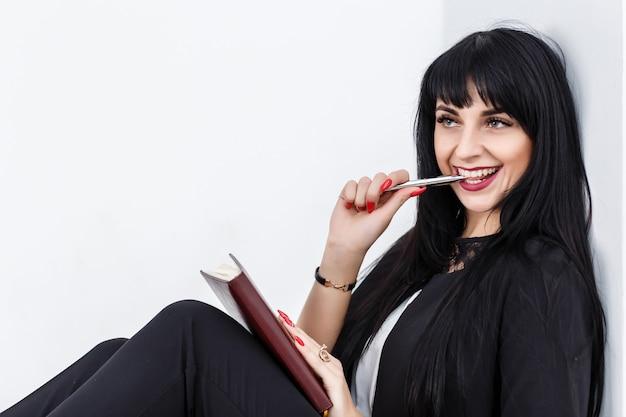 Jeune belle femme brune heureuse tenant un cahier vêtu d'un costume noir assis sur un sol dans un bureau, souriant,