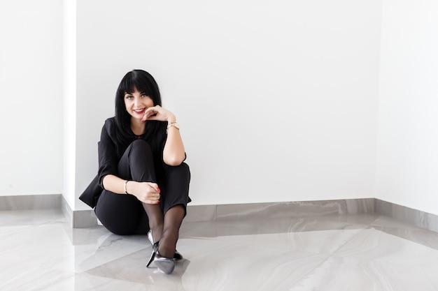 Jeune belle femme brune heureuse vêtue d'un costume noir assis sur un sol en bureau