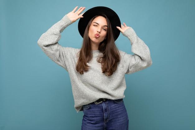 Jeune belle femme brune à la mode femme en pull gris décontracté et élégant chapeau noir positif