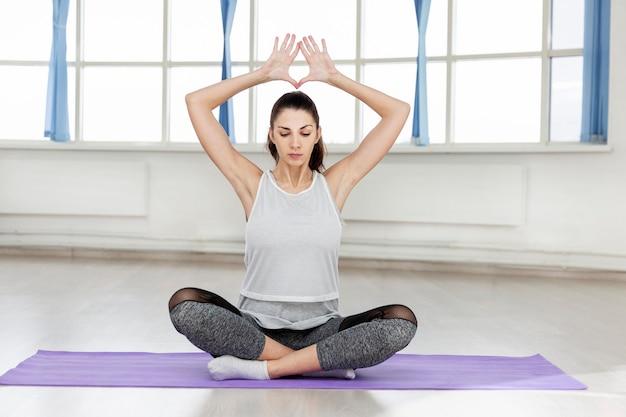Jeune belle femme brune pratique le yoga dans le hall.