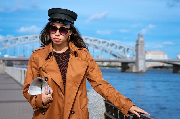 Jeune belle femme caucasienne dans une casquette noire et des lunettes de soleil dans un manteau sur le remblai posant avec un journal à la main contre le mur d'un ciel bleu et d'un pont